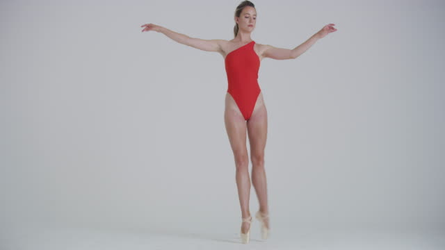ballet dancer dancing in studio performing on pointe and does a passé movement - white background stock videos & royalty-free footage
