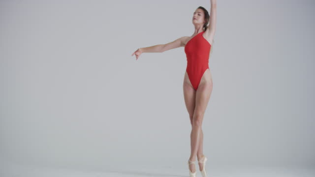 ballet dancer dancing in studio performing on pointe wearing a red leotard - ballet dancer stock videos & royalty-free footage