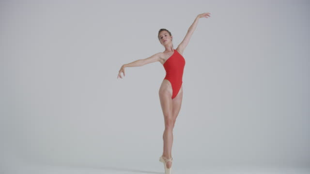 ballet dancer dancing in studio performing on pointe wearing a red leotard - leotard stock videos & royalty-free footage