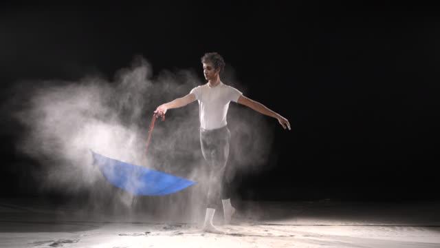 vídeos y material grabado en eventos de stock de bailarín de ballet clásico, baile con nieve polvo y paraguas en el estudio. cámara lenta - paraguas