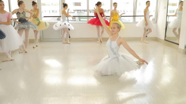 ballett tänzerin mädchen im weißen kleid auf dem boden sitzend - ballettschuh stock-videos und b-roll-filmmaterial
