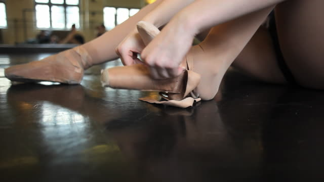cu ballet dancer laces pointe shoe onto her foot before beginning of ballet class / chicago, illinois, usa - ballet shoe stock videos and b-roll footage