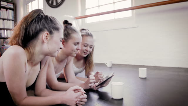 stockvideo's en b-roll-footage met ballet dancer looking at digital tablet - op de buik liggen
