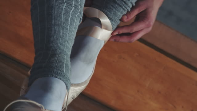 ballet dancer tying ribbon on her shoe in studio - ballet shoe stock videos & royalty-free footage