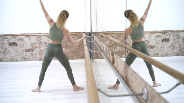 a ballet dancer warming up in front of a mirror. - barre stock videos & royalty-free footage