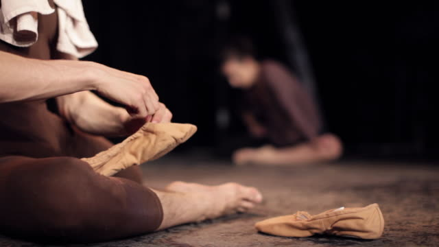 vidéos et rushes de ms tu td ballet dancers preparing on stage, man in foreground stretches his shoes and puts them on / new york city, new york, usa - danseuse classique