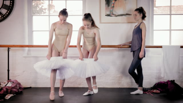 Ballet dancers putting tutu on