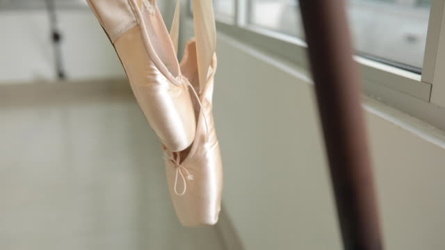 vídeos de stock e filmes b-roll de ballet shoes hanging on a barre - estúdio de dança