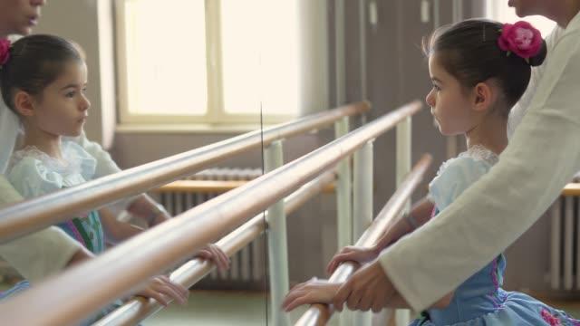 ballettlehrerin hilft mädchen mit körperhaltungen während des ballettunterrichts - flexibilität stock-videos und b-roll-filmmaterial