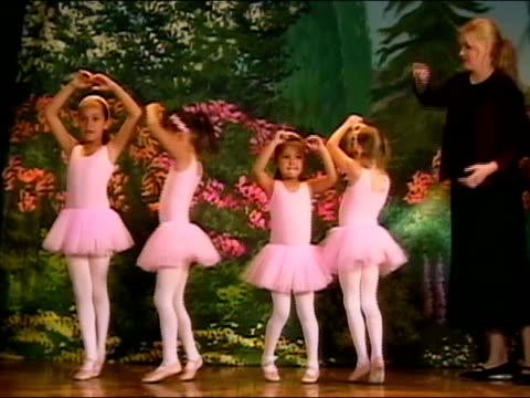 Ballet teacher ushering girls onto stage during dress rehearsal / girls dancing / curtseying / girl falling down / Los Angeles, California
