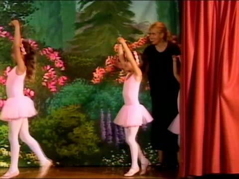 Ballet teacher ushering girls onto stage during dress rehearsal / girls dancing / Los Angeles, California