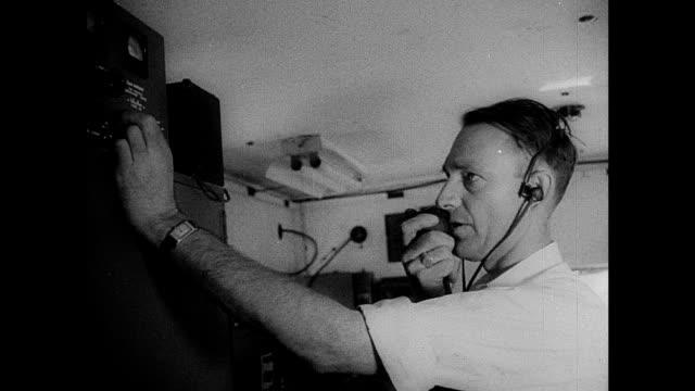 ballistic missle v2 rocket tilted up on meillerwagen in rural setting w/ mountains bg male in headset talking into mic control for setting position... - lenkflugkörper stock-videos und b-roll-filmmaterial