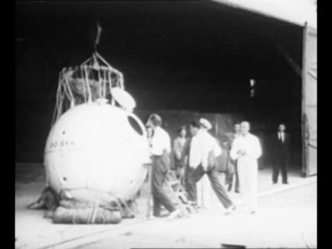 balloon crew with spherical aluminum gondola invented by auguste piccard / piccard with group of men he wears suspenders / piccard and others... - 発明家点の映像素材/bロール