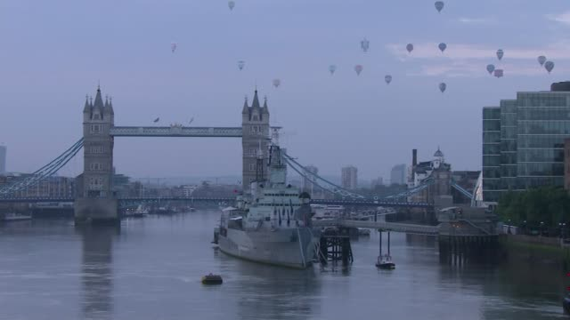 balloon regatta flies over london england london ext hot air balloons flying over river thames with towert bridge in foreground high angle shot... - itv london tonight weekend点の映像素材/bロール
