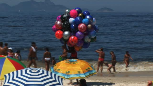 ws pan balloon vendor on copacabana beach, rio de janeiro, brazil - mercante video stock e b–roll