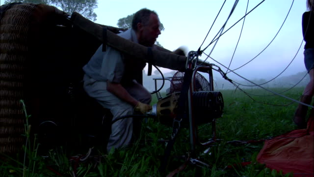 vídeos y material grabado en eventos de stock de a balloonist shoots flames toward a collapsed hot air balloon. - globo aerostático