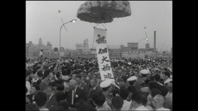 balloons and a banner float above a crowd at the opening ceremony of the tsukuda-ohashi. - 1964 stock videos and b-roll footage