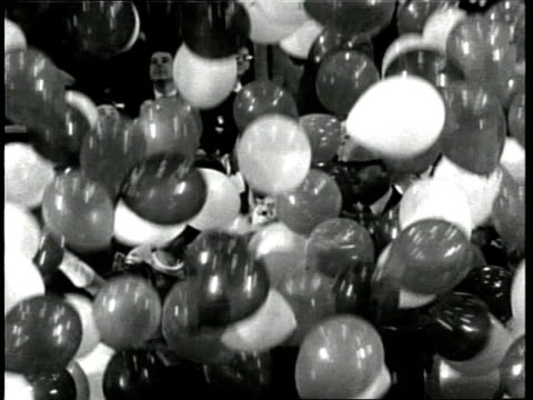 vídeos de stock e filmes b-roll de balloons fall on u.s. senator barry goldwater and his wife, margaret, as they stand at a podium during the 1964 republican national convention. - 1964