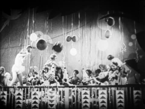 b/w 1928 balloons falling over band in clown costumes playing in nightclub / newsreel - human age stock videos & royalty-free footage