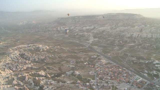 vidéos et rushes de balloons flying over rocky valley in cappadocia, turkey - strate géologique