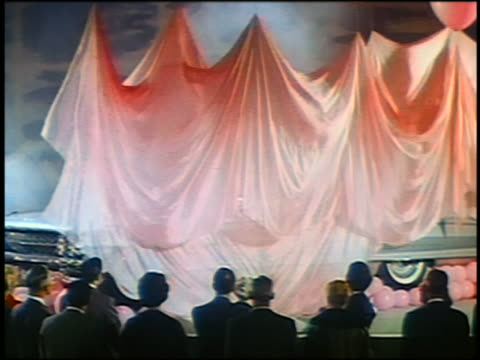 1961 balloons lifting veil over Cadillac with couple in back seat / audience in foreground / industrial