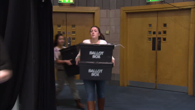 vídeos de stock, filmes e b-roll de ballot boxes arrive in birmingham ready for counting shows interior shots ballot boxes arriving at counting hall carried by volunteers on may 07 2015... - título de eleitor