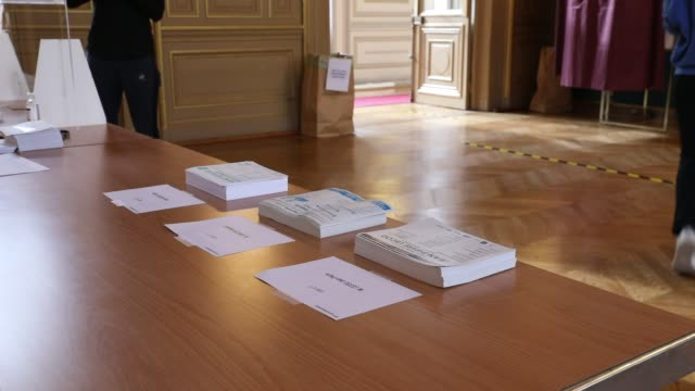 ballots are picked up before a voter enters a booth as parisians vote in the second round of municipal elections at the 6th district town hall... - ballot box stock videos & royalty-free footage