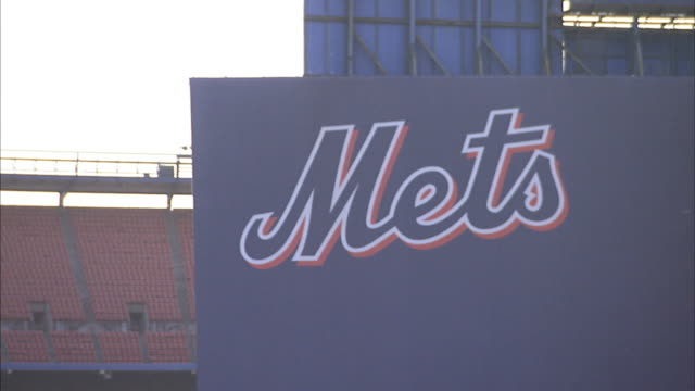 vídeos de stock, filmes e b-roll de ws ballpark tiered seating beyond partial exterior baseball park field wall w/ painted mets sign no people red blue queens flushing meadowscorona... - flushing meadows corona park