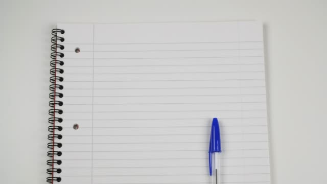 ballpoint pen rolls onto lined notepad with copy space - diary stock videos & royalty-free footage