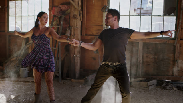 SLO MO. Ballroom dance partners perform passionate routine while kicking up sawdust in rustic barn.