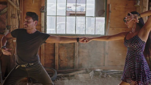 Ballroom dance partners share a passionate dance in rustic abandoned warehouse.