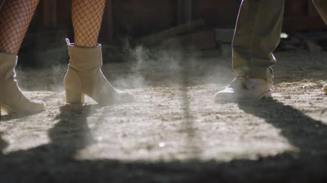 cu slo mo. ballroom dancers kick up dust as they approach each other on rustic barn floor. - 埃点の映像素材/bロール