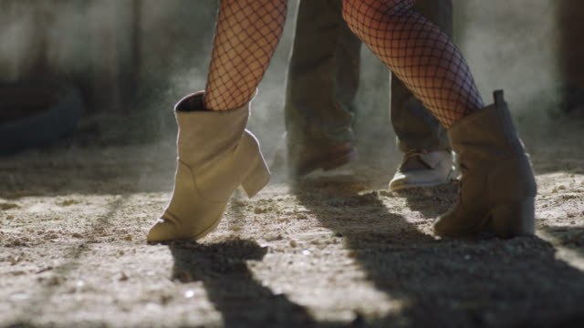 CU. Ballroom dancers kick up dust with their boots as they dance on rustic barn floor.