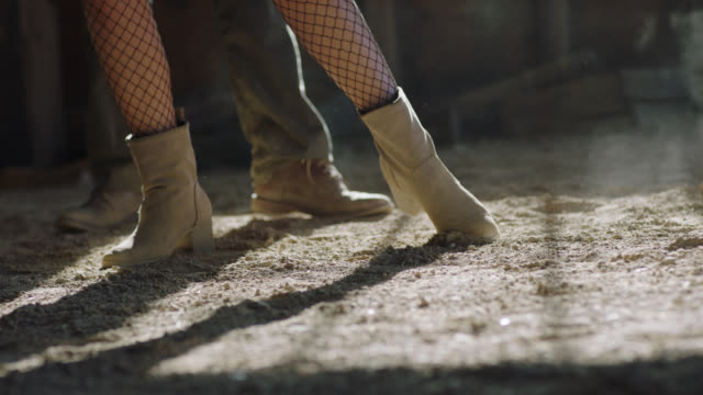 CU SLO MO. Ballroom dancers stomp, twirl, drag, and pose with their feet on dusty barn floor.