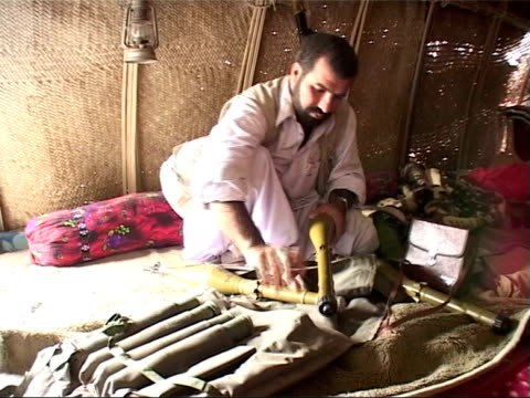 balochi militants training; more of insurgents organising their weapons inside tent, including missiles, missile launchers / back view iranian woman... - cartridge stock videos & royalty-free footage