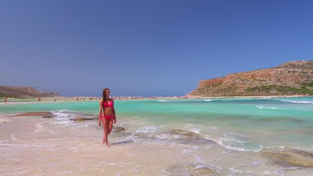 vidéos et rushes de plage de balos. crète, grèce. la jeune fille est à pied le long du littoral. drone aérien tourné. - grèce