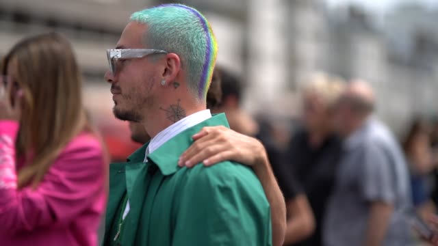 balvin wears mirror sunglasses a green long jacket a white shirt long pants sneakers with pink shoelace outside kenzo during paris fashion week... - fashion week stock videos & royalty-free footage