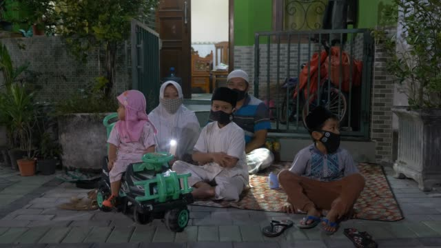 bambang gunawan's family sit in front of their home as they celebrate eid alfitr following the government measure to celebrate eid alfitr at home to... - indonesian culture stock videos & royalty-free footage