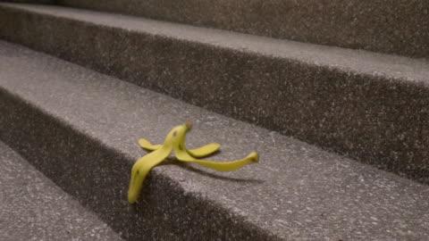 stockvideo's en b-roll-footage met banaan schillen vallen op trap slomo - pellen