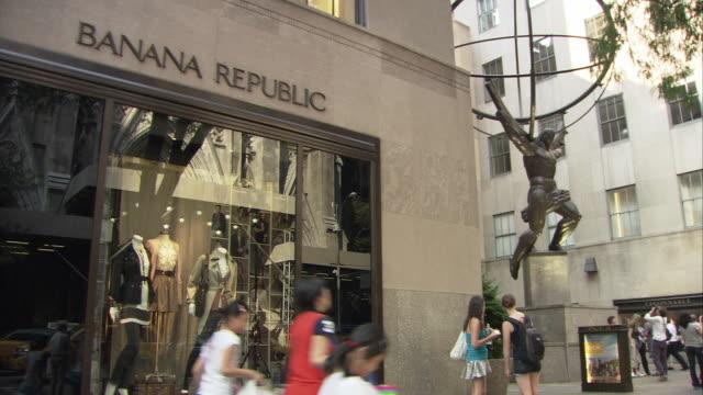 vídeos de stock e filmes b-roll de ms banana republic outside rockefeller center, statue of atlas seen in background, pedestrian traffic in front / manhattan, new york city, new york, usa - estátua de atlas