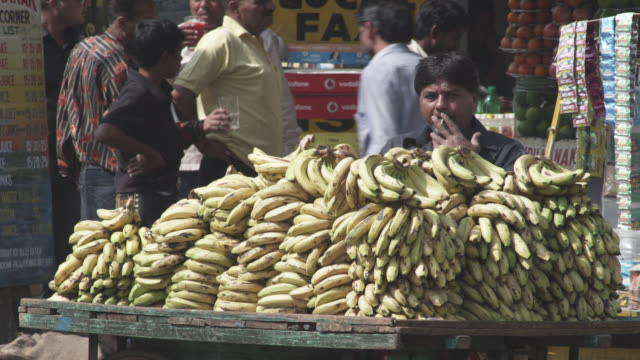 WS Banana vendor by his cart on street smoking cigarette / Patna, Bihar, India