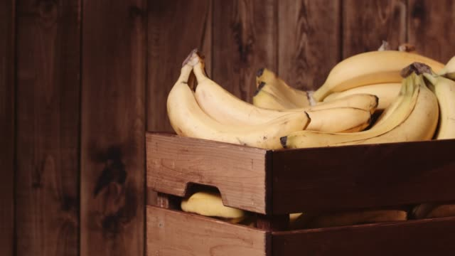 bananas in a crate on rustic wood table - banana stock videos & royalty-free footage