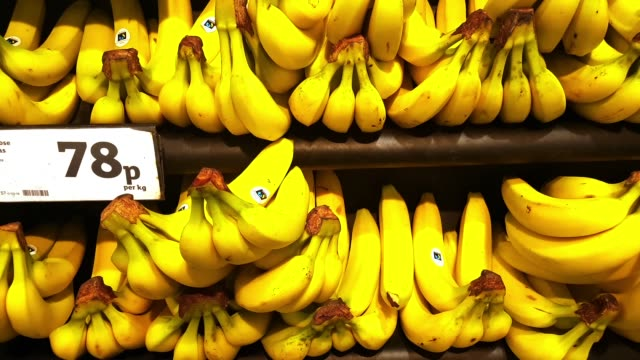 bananas on supermarket display - espositore per negozio video stock e b–roll