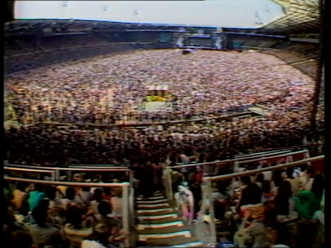 band aid record piracy tx 13785 itn ts mass crowd at live aid concert ms status quo performing tms crowd being sprayed with water - wohltätigkeit stock-videos und b-roll-filmmaterial