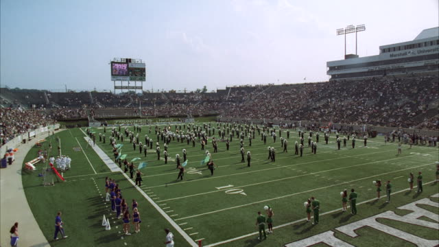 ws band in football stadium with people / unspecified - banda che marcia video stock e b–roll