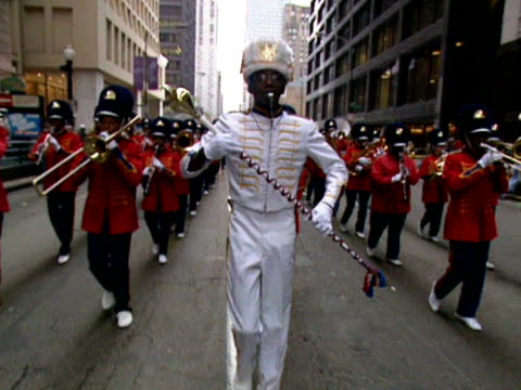 a band leader blowing a whistle leads a marching band along a street in chicago during the columbus day parade. - marching band stock videos & royalty-free footage