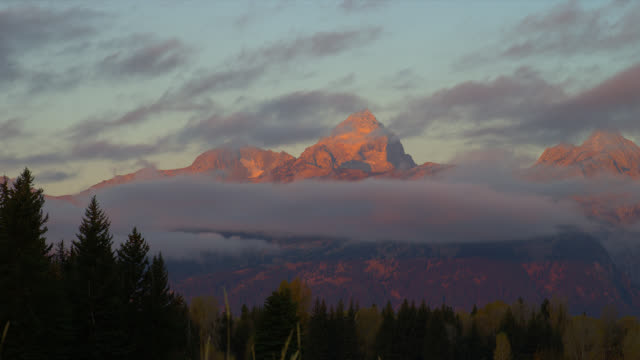 A band of clouds encircles the Grand Teton Mountains in Grand Teton National Park at dawn.
