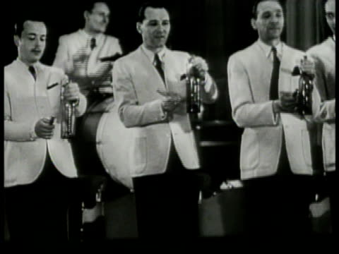vídeos de stock, filmes e b-roll de band on stage playing audience at tables w/ beer mugs watching musicians playing bottles women at table smoking cigarette two men at table young... - 1943