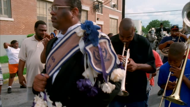A band performs on a New Orleans street. Available in HD.