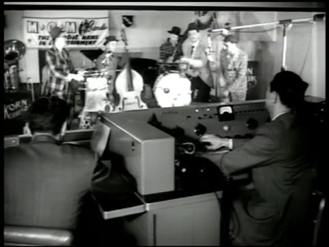 stockvideo's en b-roll-footage met band playing in recording studio ws two men at control room window band bg vs band members playing w/ bicycle horns whistle cow bells ws band... - 1949